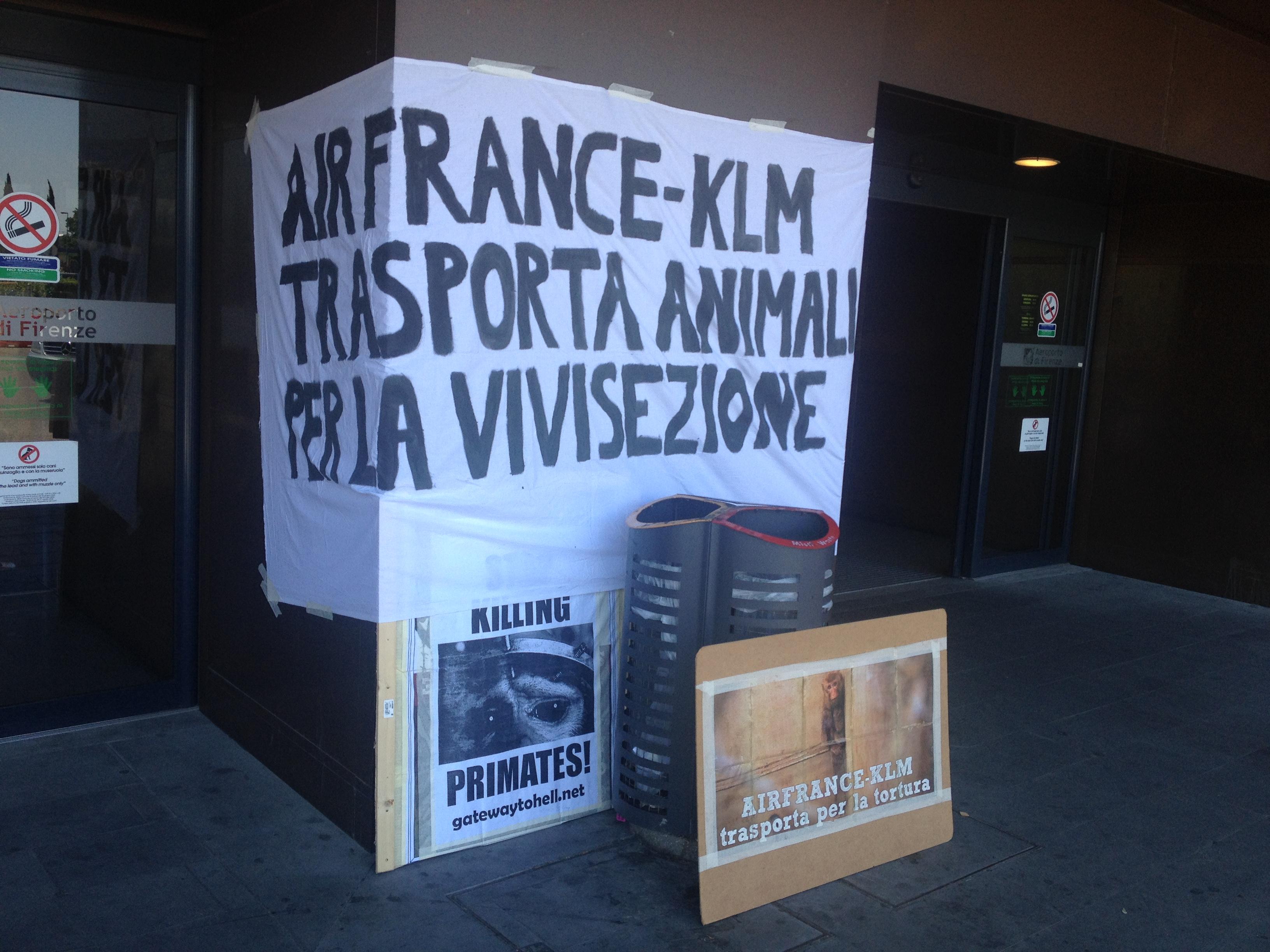 """Striscione e cartelli esposti davanti all'entrata principale dell'aeroporto """"Amerigo Vespucci"""" di Firenze"""